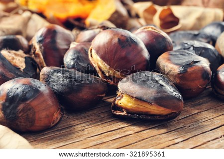 closeup of some roasted chestnuts on a rustic wooden table with some roasted sweet potatoes and autumn leaves in the background - stock photo