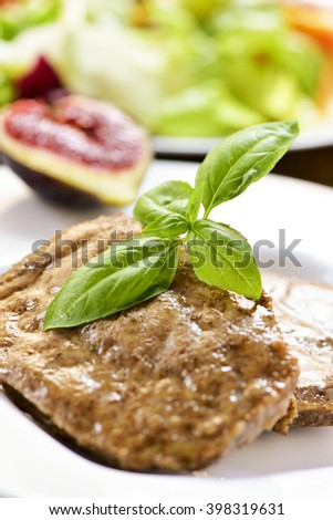 closeup of some seitan burgers in a ceramic plate, on a set table next to other vegetarian food - stock photo