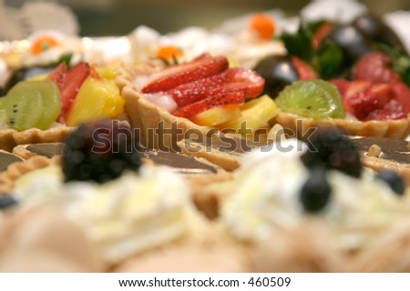 Closeup of some sweet treats, including strawberries, tarts, raspberry, kiwin, and pastry. - stock photo