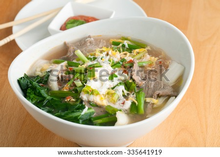Closeup of some Thai pho style soup with beef and clear rice noodles. - stock photo
