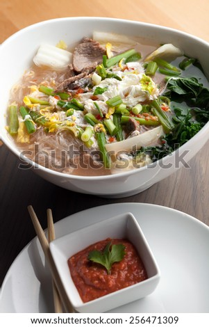 Closeup of some Thai pho style soup with beef and clear rice noodles. Sriracha dipping sauce. - stock photo