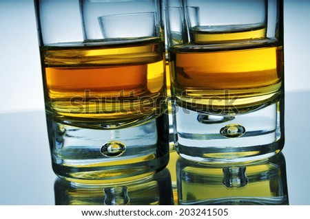 closeup of some wisky shots on a reflecting surface - stock photo
