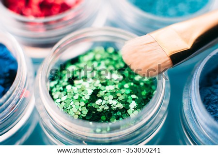 closeup of sparkling glitter eyeshadow set. Collection of  colorful shiny green, red and blue shadows. Makeup artist background. - stock photo