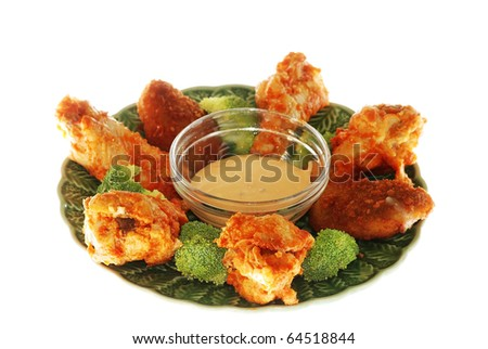 Closeup of spicy buffalo chicken wings and jalapeno pepper poppers with spicy dip and broccoli sprigs isolated on green plate with dipping sauce.