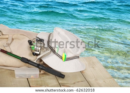 closeup of spinning fishing equipment on a dock - stock photo
