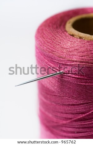 Closeup of spool of thread with needle