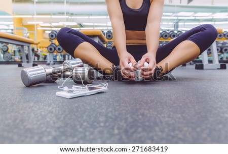 Closeup of sporty woman sitting on the floor of fitness center with dumbbells and smartphone with earphones in the foreground - stock photo