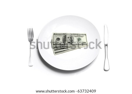 Closeup of stack of cash isolated on white plate with silverware