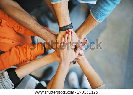 Closeup of stack of hands. Young college students putting their hands on top of each other symbolizing unity and teamwork. - stock photo