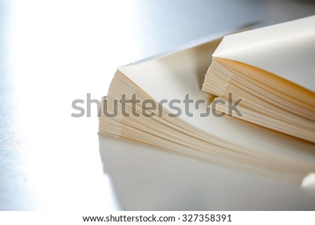 Closeup of stacked papers on table - stock photo