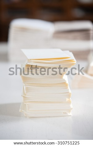Closeup of stacked white papers on table in factory - stock photo