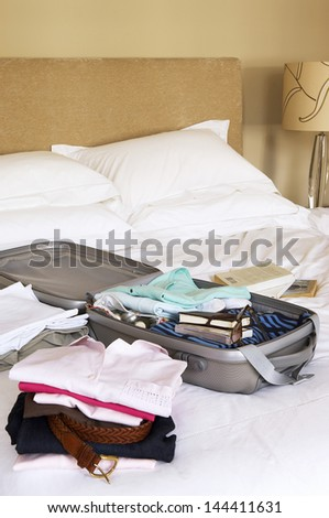 Closeup of stacks of folded clothes and packed suitcase on bed - stock photo