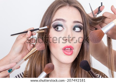 closeup of stunned beautiful blond girl getting hair and makeup done isolated over white - stock photo