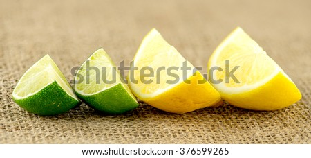 Closeup of succulent wedges of lemons and limes - stock photo