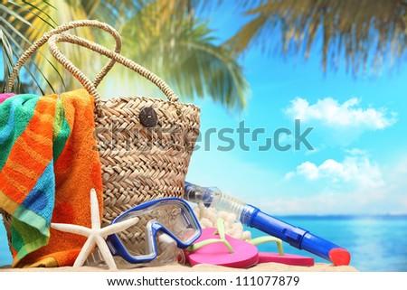 Closeup of summer beach bag on sandy beach. - stock photo