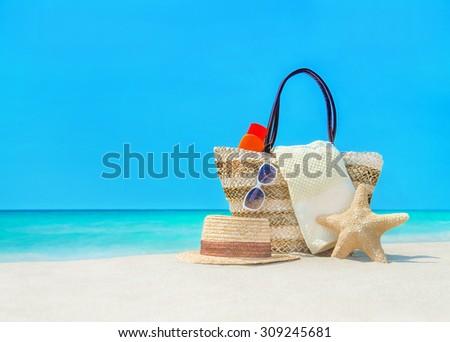 Closeup of summer straw bag, hat, sun protection cream, towel and sunglasses on sandy beach - stock photo