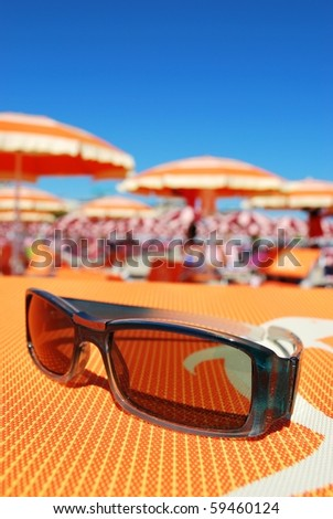 Closeup of sunglasses and beach with orange umbrellas in background, Rimini, Italy - stock photo