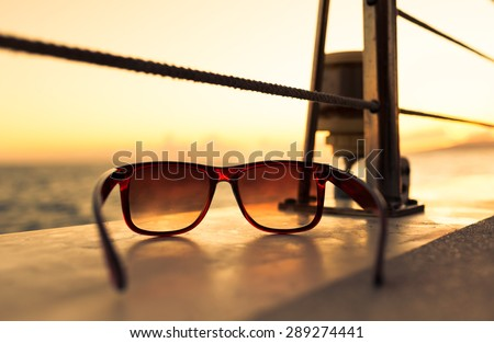 Closeup of sunglasses on a boat at sunset.  - stock photo