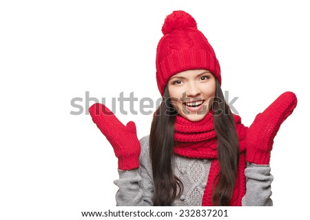 Closeup of surprised young female wearing warm winter red hat, gloves and scarf
