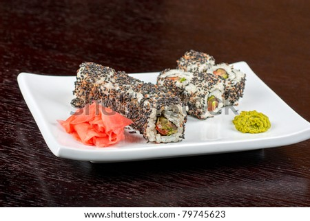 Closeup of Sushi rolls at plate with sesame - stock photo