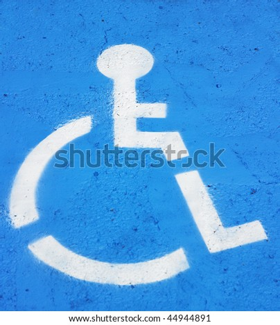 Closeup of symbol indicating handicapped parking painted on the pavement. Vertical shot. - stock photo