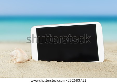Closeup of tablet computer and shell on sand at beach - stock photo