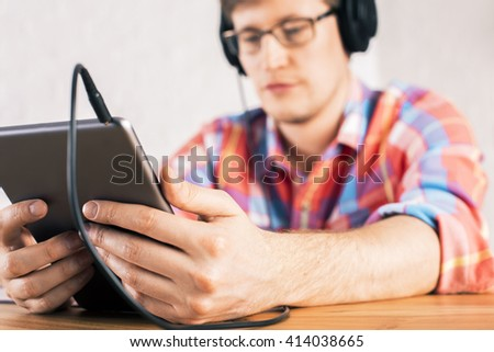 Closeup of tablet in hands of caucasian male who is listening to music - stock photo
