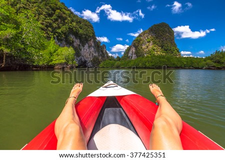 Closeup of tanned and sexy woman's legs with anklets on a red kayak in the famous mangroves of Ao Phang Nga Bay National Park, Krabi, Thailand. - stock photo
