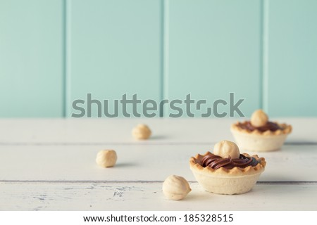 Closeup of tartlets with chocolate and hazelnut cream on a white wooden table with a robin egg blue background. Vintage look. - stock photo