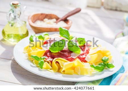 Closeup of tasty pappardelle pasta with tomato and parmesan - stock photo