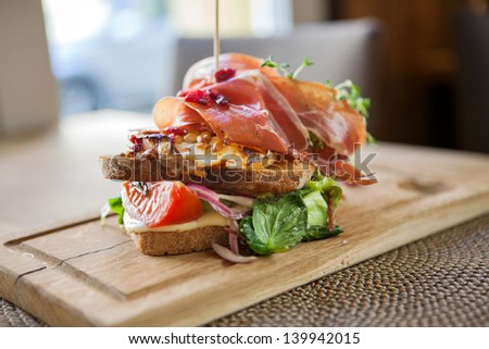 Closeup of tasty parma ham sandwich on wooden plate at cafe - stock photo