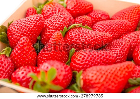 Closeup of tasty spanish strawberries freshly collected on a wooden box - stock photo