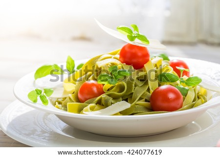 Closeup of tasty tagliatelle with tomatoes and parmesan - stock photo