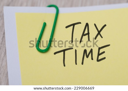 Closeup of Tax Time written on yellow paper note with paperclip - stock photo