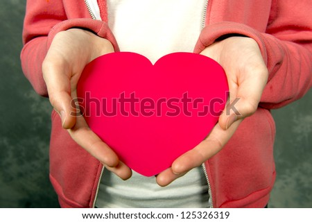 Closeup of teen girl in pink hoodie holding red heart - stock photo