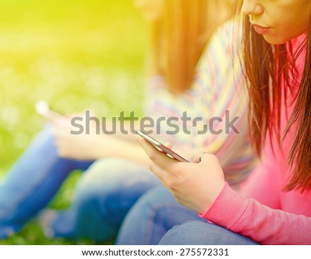 Closeup of teenage girls hands using cell phones outdoors - stock photo