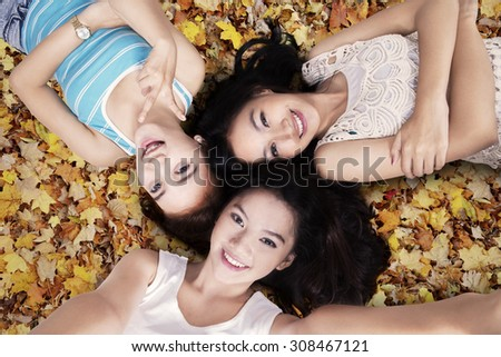 Closeup of teenage girls lying down on the autumn leaves and taking self picture together - stock photo