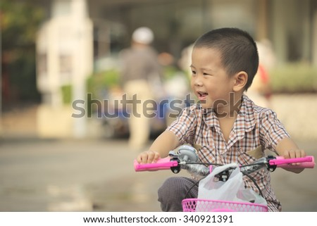 Closeup of Thai boy riding new bicycle with white plastic shopping back inside basket.