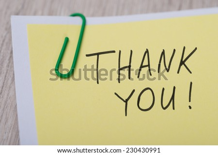 Closeup of Thank You ! written on yellow paper note with paperclip - stock photo