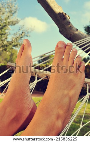 closeup of the bare feet of a man who is relaxing in a hammock - stock photo