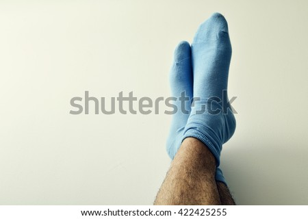 closeup of the bare legs of a young man wearing blue socks with his feet against the wall - stock photo