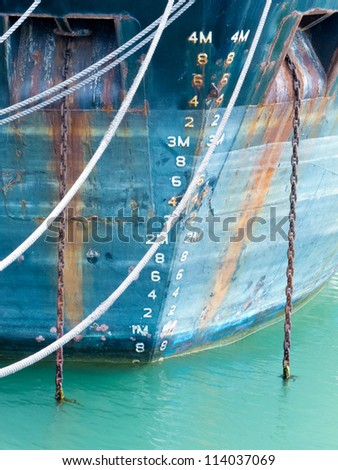 Closeup of the bow hull with floatation depth scale gauge of a ship with grungy rust streaks from corroded anchor chains - stock photo
