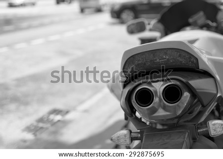 Closeup of the exhaust pipes of motorcycle, parked on a street, city traffic in the blurred background - stock photo