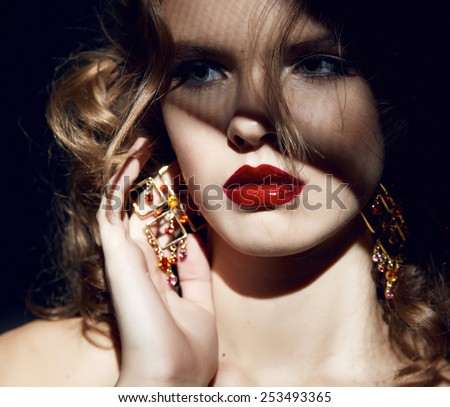 Closeup of the face belong to beautiful young sexy blonde girl with curly hair pure snow white skin and bright makeup red lips, red lipstick, long earrings in dark shadows of palm leaves