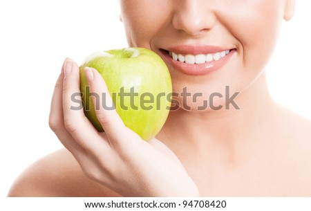 closeup of the face, hands and healthy white teeth of a woman holding an apple, isolated against white background - stock photo