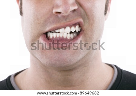 closeup of the face of a snarling young man expressing anger - stock photo