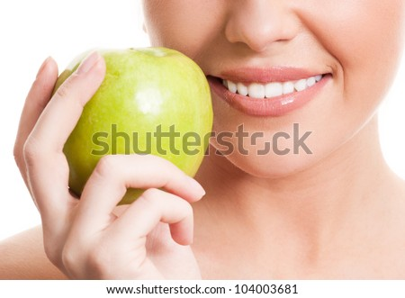 closeup of the face of a woman holding a green apple, isolated against white background - stock photo