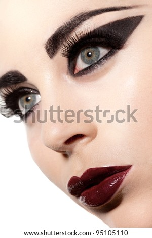 Closeup of the facial features of a beautiful sultry woman in creative Gothic makeup - stock photo