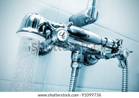 closeup of the faucets of a shower with a shower hand - stock photo
