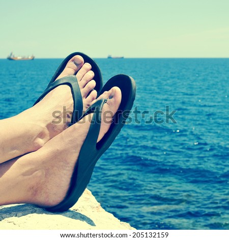 closeup of the feet of a man with flip-flops who is relaxing near the ocean in the summer, with a retro filter effect - stock photo